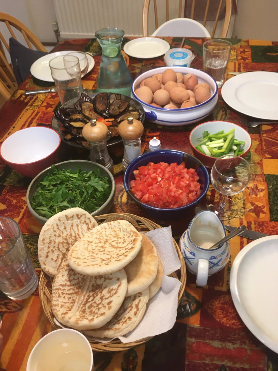 A table laid with red eggs, babinjan, chopped tomatoes, parsley, spring onions and pita