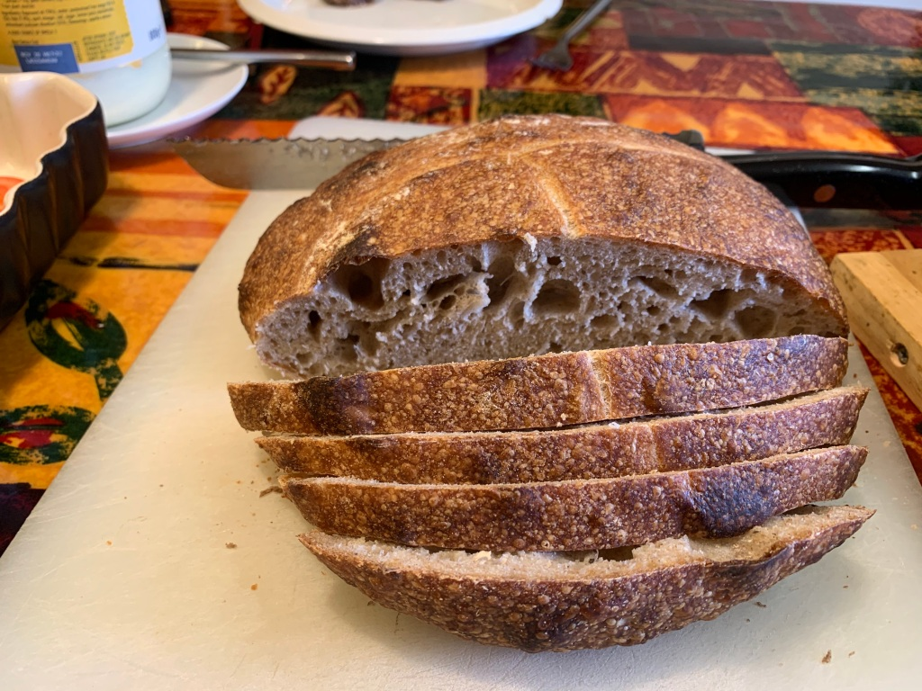 Loaf of bread with slices in the foreground. Shows the large bubbles in the bread